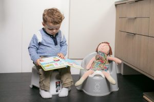 Potty Training: toddler with book and doll